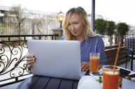 Female blogger working in coffee shop, using laptop - AZF00077
