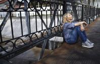 Blond woman sitting on bridge, taking a break - AZF00080