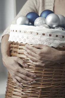 Woman carrying basket full of Christmas baubles - AZF00083