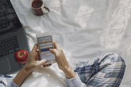 Woman sitting on bed with laptop, reading text messages - AZF00092
