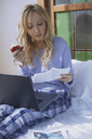 Woman sitting on bed with laptop, reading papers, eating apple - AZF00095