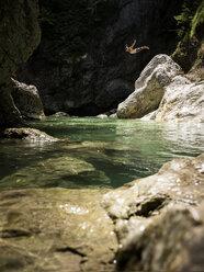 Man jumping from rock into brook - CVF01064