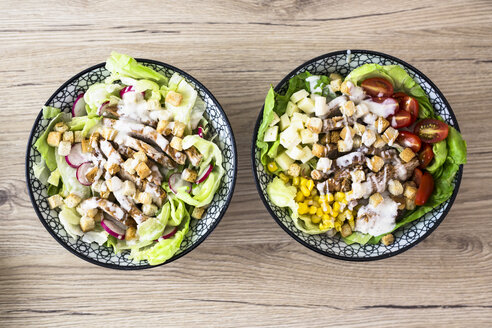 Two bowls of various Caesar salads with meat - GIOF04133