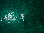 Croatia, Cres, Adriatic Sea, Aerial view of man lying on paddleboard - DAWF00706