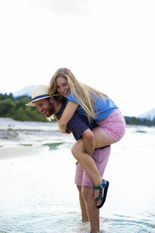Young man giving girlfriend piggyback ride, river - MAEF12700