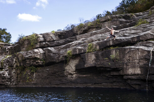 Young man jumps off rock cliffs into a lagoon at High Falls Park, Geraldine, Alabama. - AURF00261