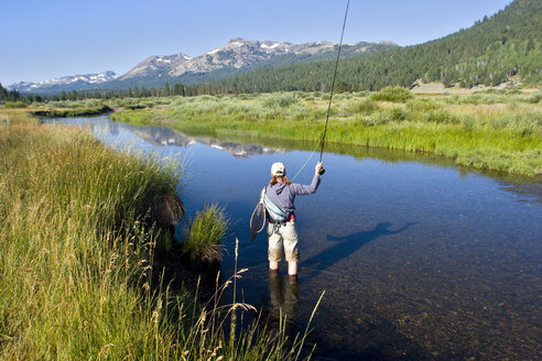 Young woman fly fishing the West Fork of the Carson River in Hope Valley. Lake Tahoe, California. - AURF00288