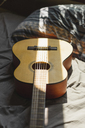 Acoustic guitaron top of a bed with sunlight - AFVF01395