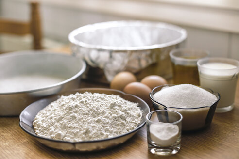 Ingredients for a cake, wheat flower, sugar, milk and eggs on pastry board - ACPF00230