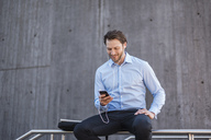 Smiling businessman with earbuds sitting on a railing looking at smartphone - DIGF04808