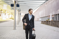 Businessman on the move pushing rolling suitcase - DIGF04829