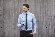 Businessman standing at concrete wall holding smartphone - DIGF04847