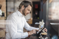 Businessman using tablet in a cafe - DIGF04859