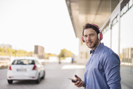 Smiling man listening to music with headphones outdoors - DIGF04874