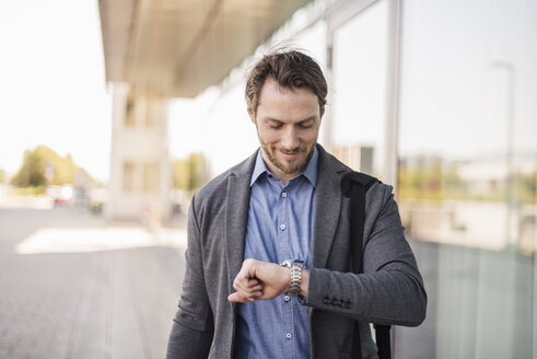 Smiling businessman with laptop bag checking the time - DIGF04877
