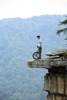 Young boy rides his mountain unicycle the trails atop Central Endless Wall at the New River Gorge near Fayetteville, WV - AURF00459