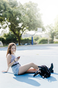 Young woman with backpack sitting on sports ground using cell phone - GIOF04146