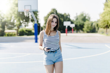 Portrait of young woman on sports ground holding cell phone - GIOF04149