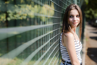 Portrait of smiling young woman standing at a fence - GIOF04152