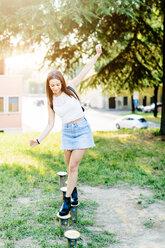 Young woman balancing on posts - GIOF04164