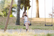 Young woman sitting on a swing on a playground - GIOF04167