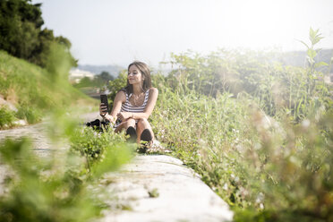 Young woman sitting in the nature using cell phone - GIOF04176