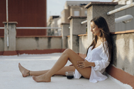 Young woman relaxing on roof terrace at sunset - AFVF01403