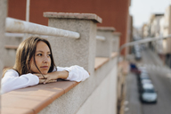 Portrait of young woman relaxing on roof terrace - AFVF01406