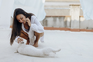 Happy young woman playing with her dog on roof terrace - AFVF01409