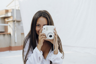Portrait of young woman taking photos with camera on roof terrace - AFVF01412