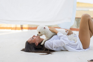 Happy young woman cuddling with dog on roof terrace - AFVF01415