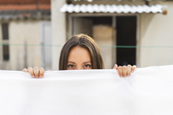 Portrait of peeking young woman behind drying bed sheet on roof terrace - AFVF01424