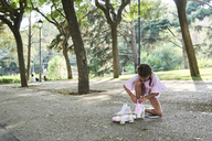 Little girl tying pink roller skates in a park - IGGF00506