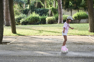 Little girl wearing braids and cap roller skating in the park - IGGF00509