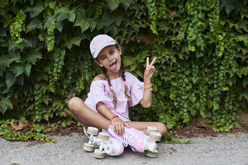 Confident little girl sticking out tongue sitting on the ground with pink roller skates - IGGF00518