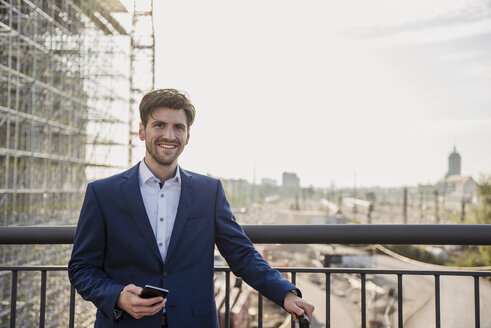 Portrait of smiling businessman standing on bridge in the city holding cell phone - DIGF04879