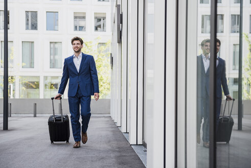 Smiling businessman with baggage in the city on the move - DIGF04906