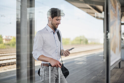 Businessman with baggage standing on station platform using cell phone - DIGF04915