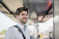 Portrait of smiling businessman on station platform with earphones - DIGF04921