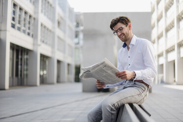 Smiling businessman sitting in the city reading newspaper - DIGF04924