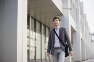 Smiling businessman with crossbody bag in the city on the move - DIGF04936