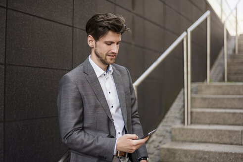 Businessman using cell phone on stairs - DIGF04939