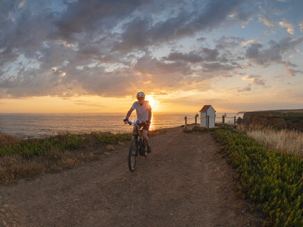 Portugal, Alentejo, senior man on e-bike at sunset - LAF02068