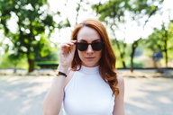 Portrait of redheaded woman wearing sunglasses - GIOF04183