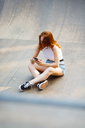 Redheaded woman using smartphone outdoors - GIOF04195
