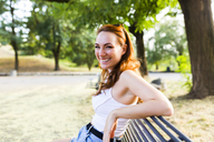 Portrait of laughing redheaded woman sitting on bench in a park - GIOF04198