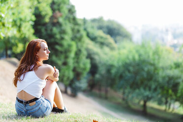 Redheaded woman relaxing on hill in a park - GIOF04204