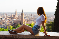Italy, Verona, redheaded woman sitting on a wall looking at view - GIOF04210