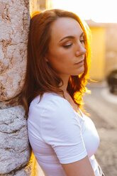Portrait of redheaded woman leaning against wall at sunset - GIOF04219