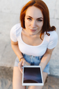 Portrait of smiling redheaded woman sitting on wall with digital tablet - GIOF04225